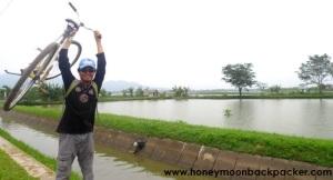 Aa mengangkat sepeda kesayangan di tepi irigasi Cikoneng.