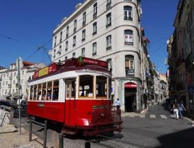 Tram listrik tua melintasi liuk jalan kota tua Lisbon